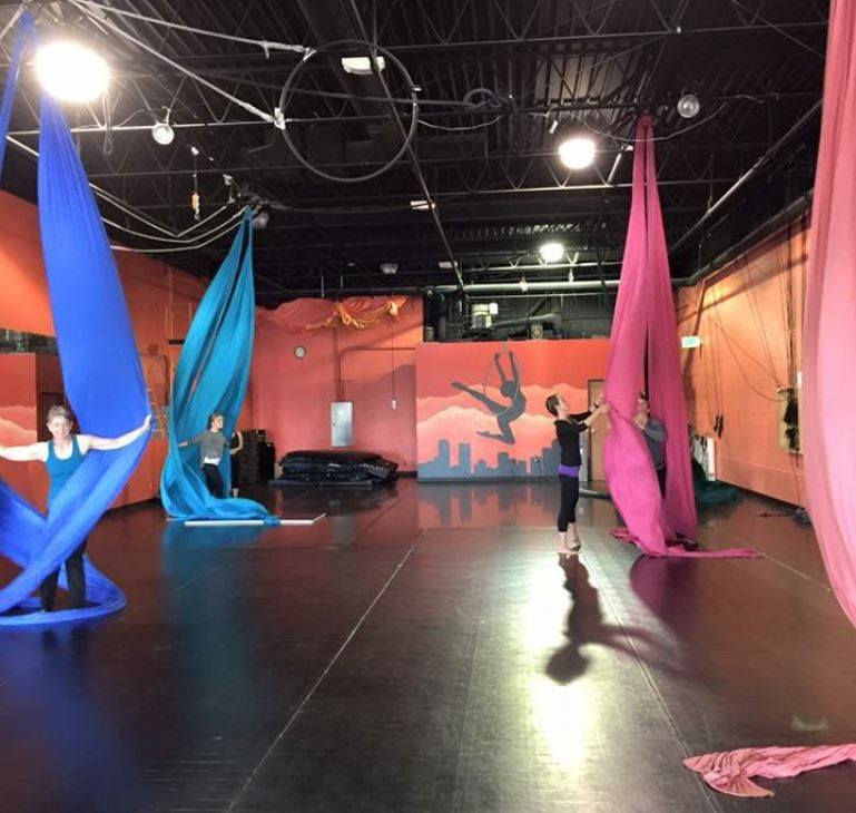 Students practicing on aerial silk in class