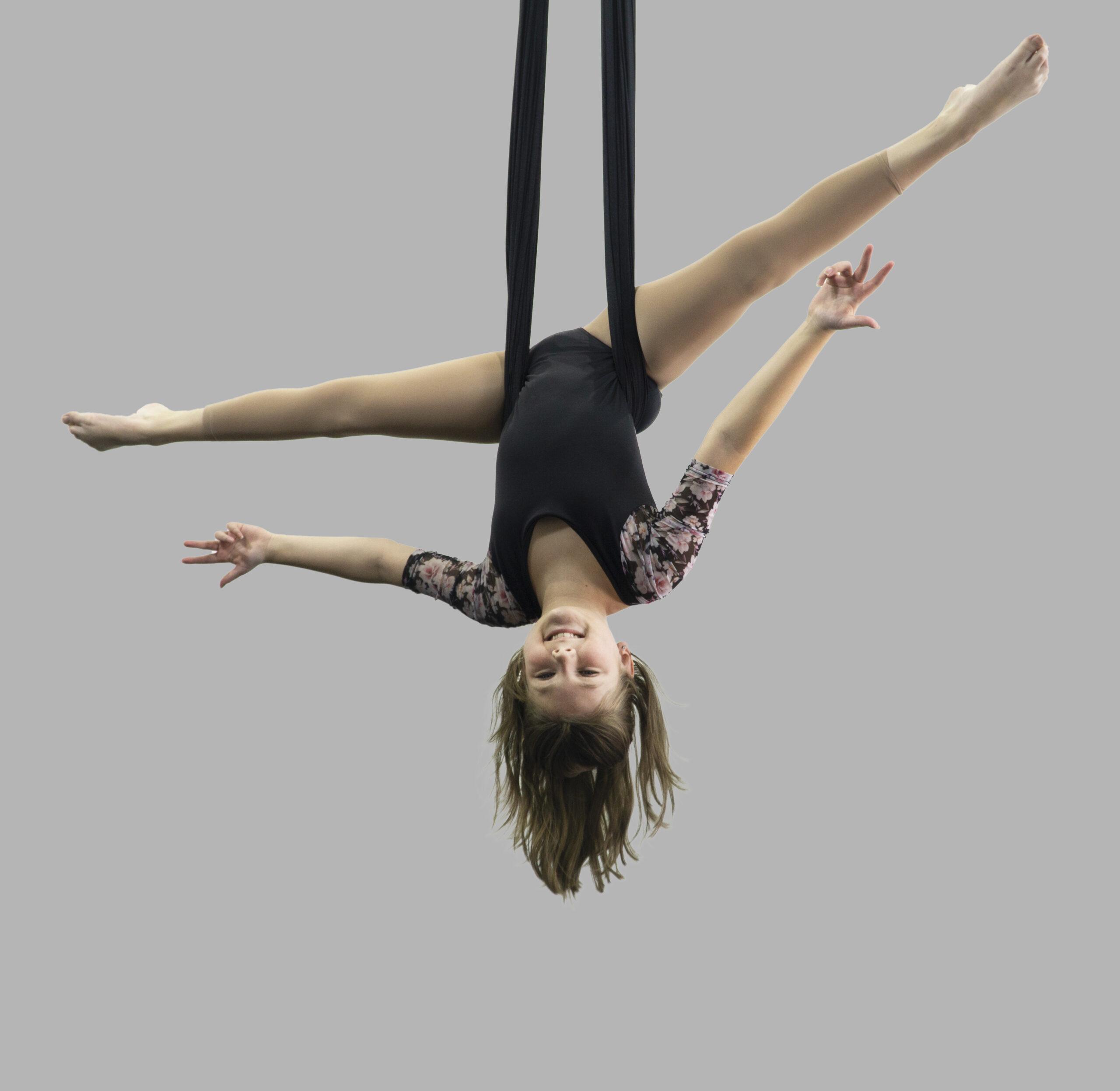 Pre-teen aerial dance student performing on silks