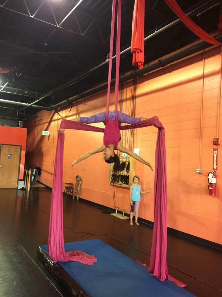 Pre-teen aerial dance student performing on silks